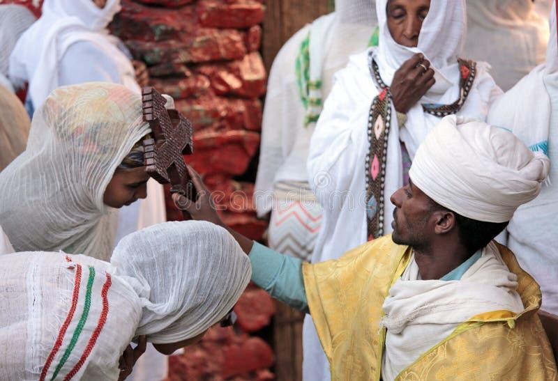 Христианский священник с большим деревянным крестом благословляет worshippers стоковое фото