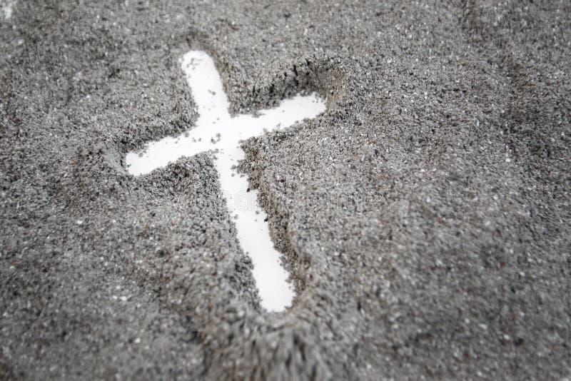 Христианский чертеж креста или распятия в золе, пыли или песке как символ вероисповедания, поддачи, redemtion, Иисуса Христа, зол стоковое фото