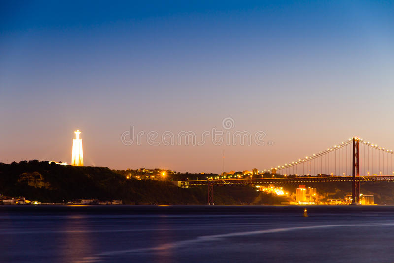 Христос статуя короля и взгляд моста 25 de Abril стоковые изображения