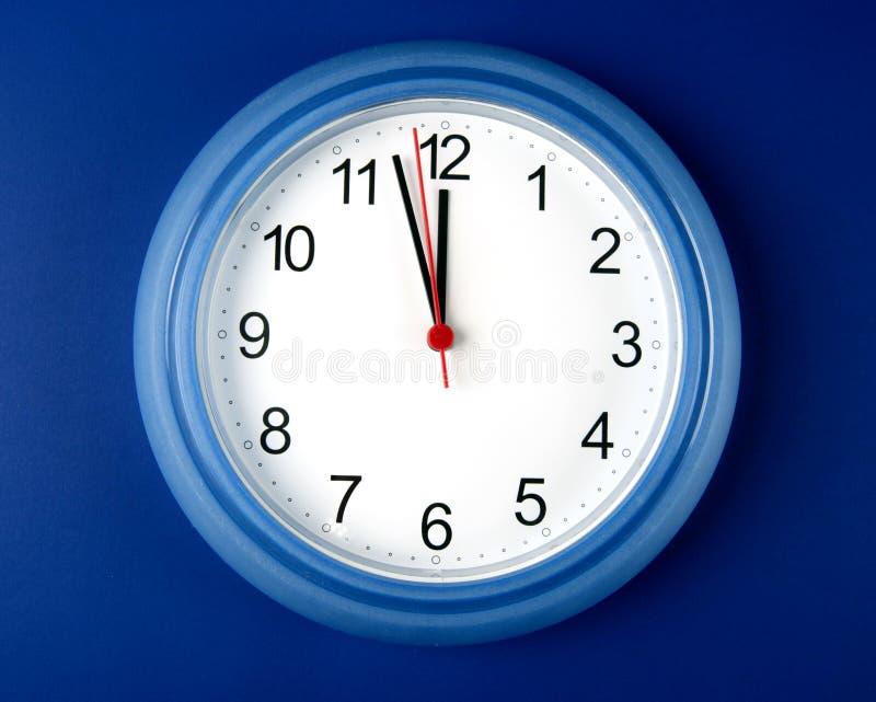 Хронометрируйте около для того чтобы ударить полночь или полдень на голубой предпосылке стоковая фотография