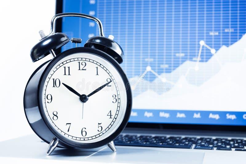 Хронометрируйте сигнал тревоги с диаграммой диаграммы запаса в предпосылке экрана компьтер-книжки стоковая фотография rf