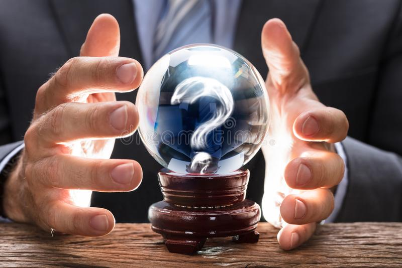 Хрустальный шар заволакивания бизнесмена с вопросительный знак стоковые изображения rf