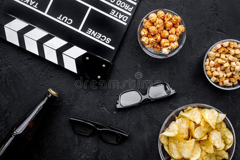 Хрустящая корочка, попкорн, сухари для смотреть фильм Clapperboard и стекла на черном взгляд сверху предпосылки стоковое изображение