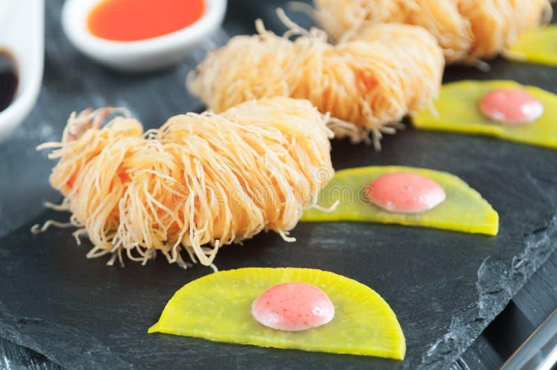Хрустящая креветка в коре Kataifi С пряными соусами и marinated daikon Темное фото на классн классном шифера стоковое изображение