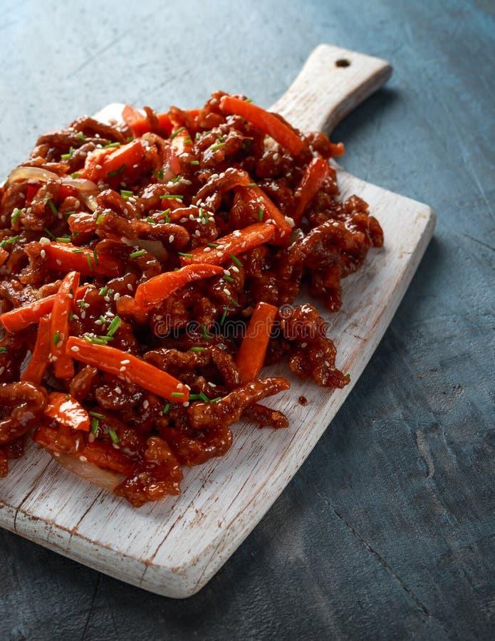 Хрустящая shredded говядина с морковами и сладким соусом чилей на белой деревянной доске Китайская на вынос еда стоковое изображение