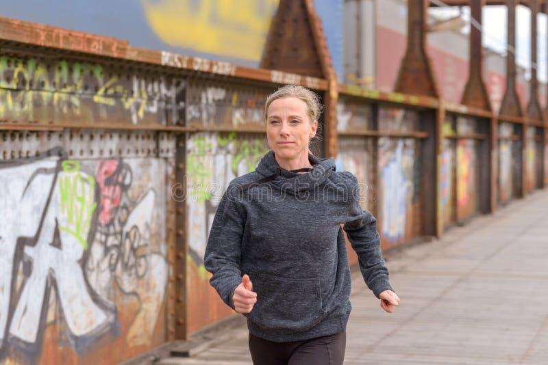 Худенькая атлетическая женщина jogging на мосте стоковое фото
