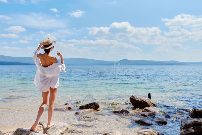 Худенькая девушка в белой рубашке и соломенной шляпе стоит с ей стоковая фотография rf