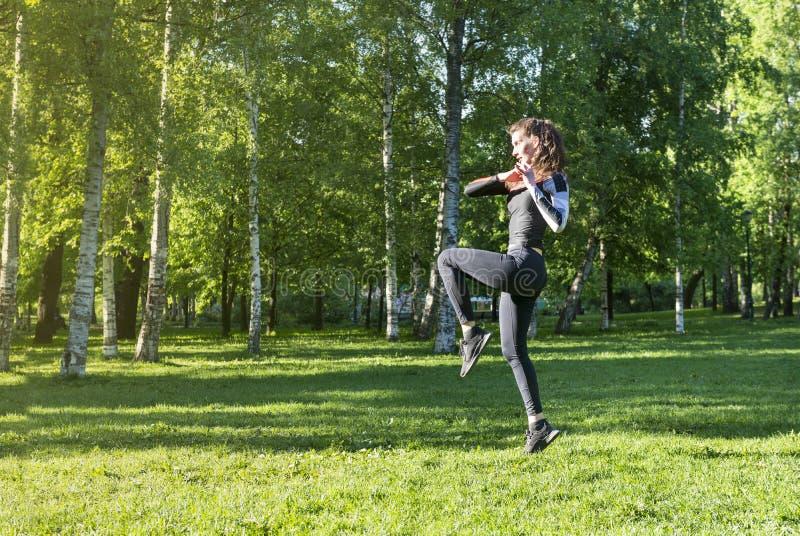 Худенькая девушка делая спорт в парке среди зеленых деревьев стоковая фотография rf