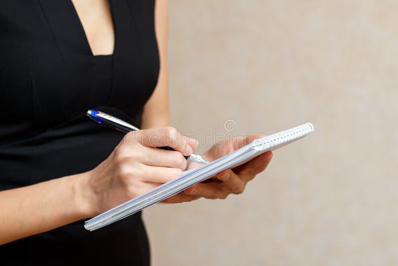 Худенькая девушка держа блокнот и ручку стоковое фото