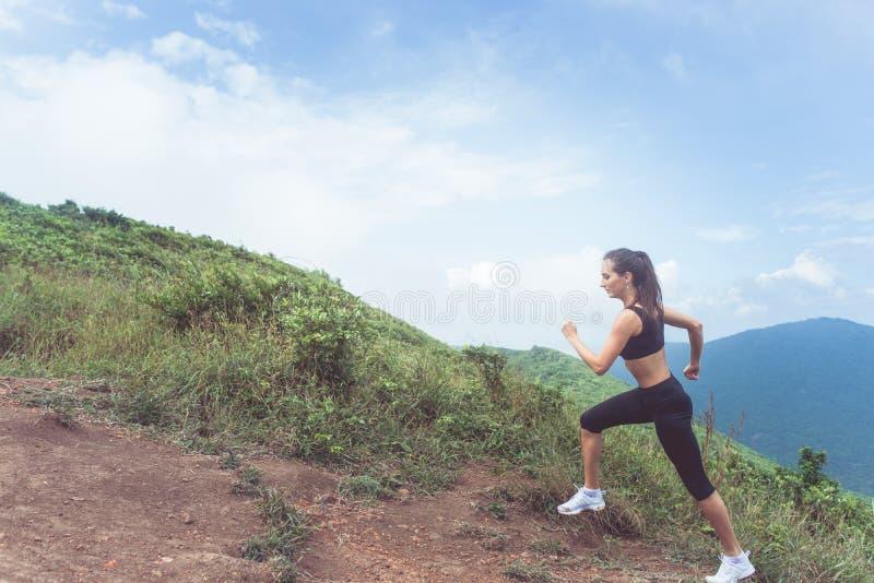 Худенькая молодая спортсменка делая cardio тренировку идя вверх гора с морем в предпосылке стоковая фотография