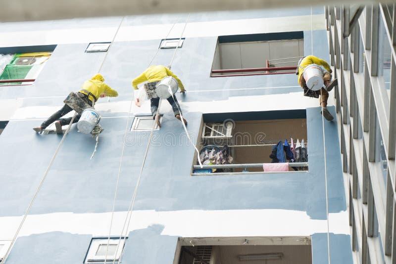 Художник вися на крене, крася цвете на стене Построитель фасада с щеткой ролика, работая на высокой строительной конструкции r стоковое фото