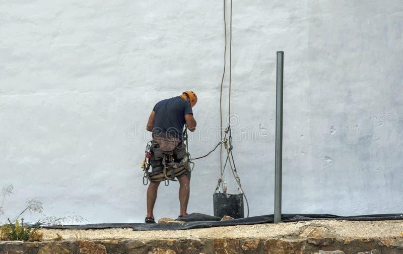Художник крася белую стену в Мурсии стоковое фото