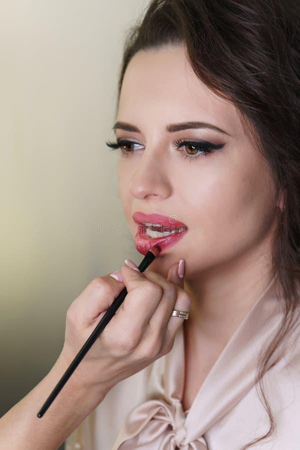 Художник макияжа работая в составляет студию стоковое фото