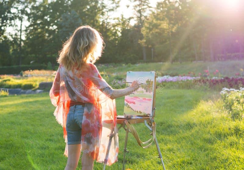 Художник молодой женщины держит щетку и красит изображение на ea стоковое изображение