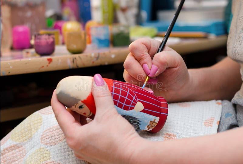 Художник рисует куклу-matryoshka Крупный план руки стоковое изображение rf