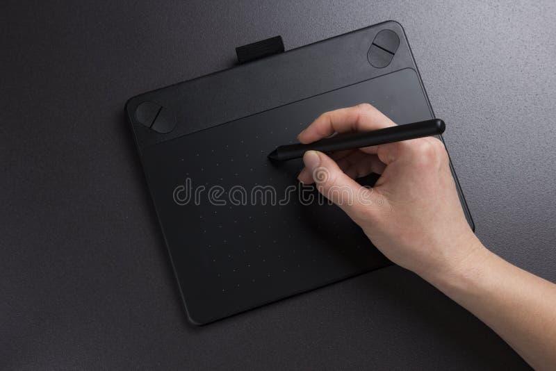 Художник рисует на графической таблетке Дизайнер работает на крупном плане графической таблетки Ручка владениями руки для краски стоковое изображение