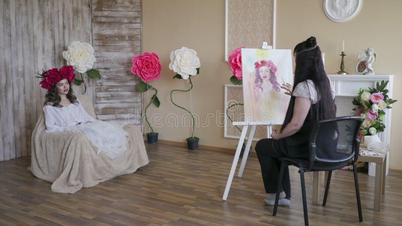 Художник рисует портрет от природы Красивая модель, при венок пионов шарлаха на его голове, представляя сидеть в a стоковое фото