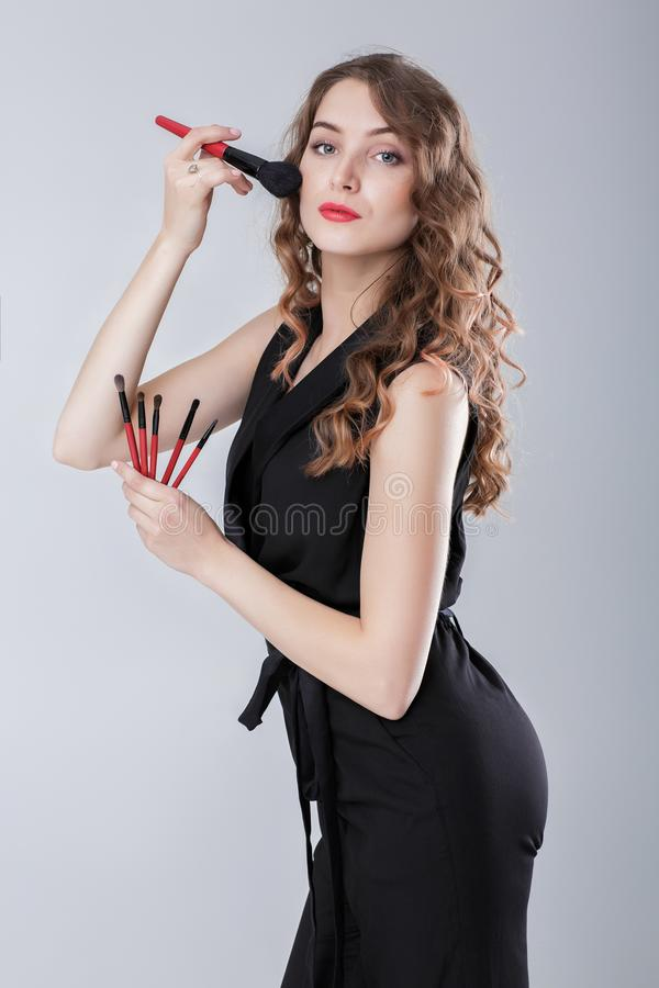 Художник состава женщины при естественный состав держа щетку состава на серой предпосылке стоковые фото
