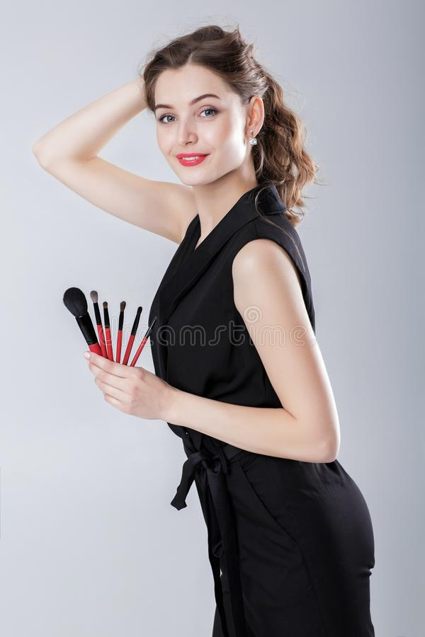 Художник состава женщины при естественный состав держа щетку состава на серой предпосылке стоковое изображение rf
