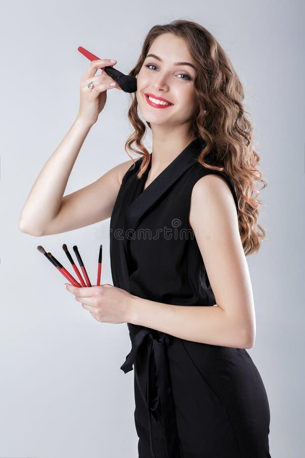 Художник состава женщины при естественный состав держа щетку состава на серой предпосылке стоковые изображения rf