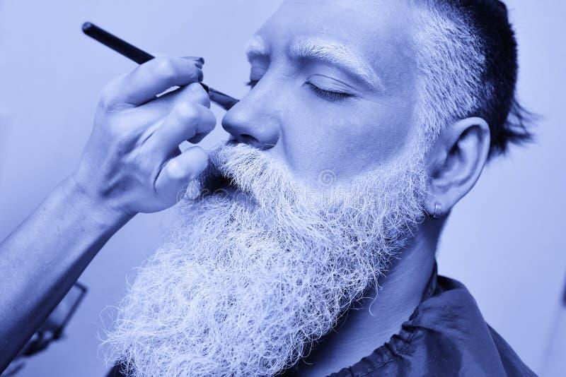 Художник состава красит бороду, усик и брови ` s человека в седом цвете стоковые фотографии rf