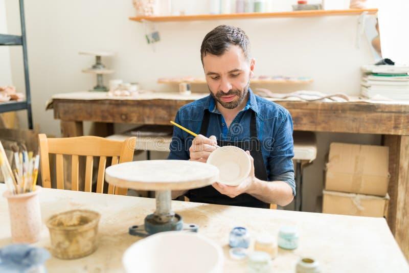 Художник украшая шар глины с краской в студии стоковое фото rf