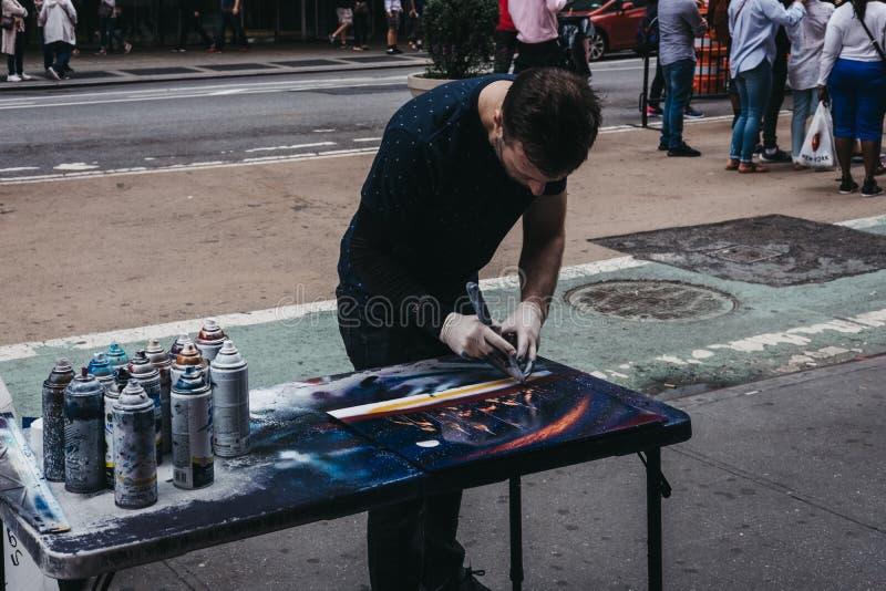 Художник улицы создавая изображение использующ с краской для пульверизатора во временах стоковое изображение rf