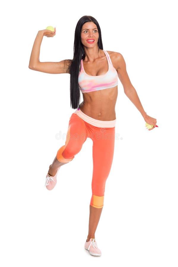 Худенькая девушка фитнеса бросает теннисный мяч стоковая фотография