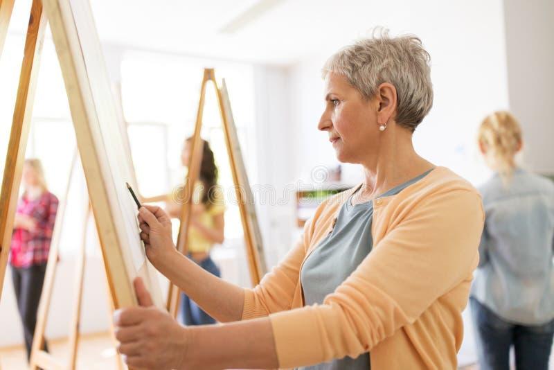 Художник женщины с чертежом карандаша на художественном училище стоковое фото