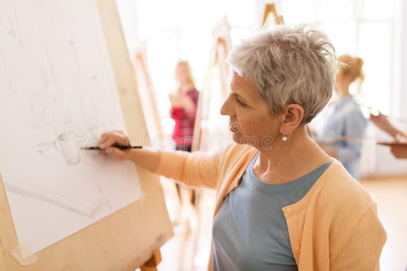 Художник женщины с чертежом карандаша на художественном училище стоковые фото