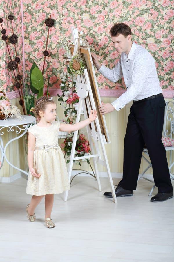 Художник красит портрет милой маленькой девочки стоковое изображение rf