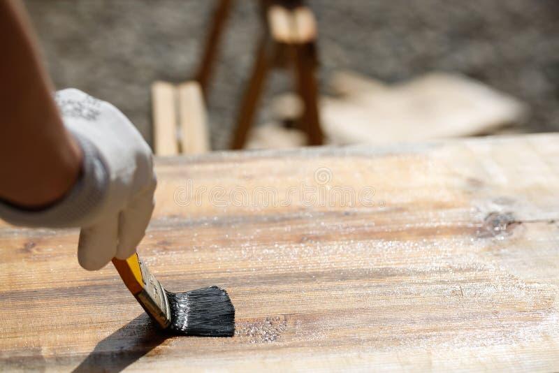 Художник крася деревянную поверхность, защищая древесину стоковая фотография rf