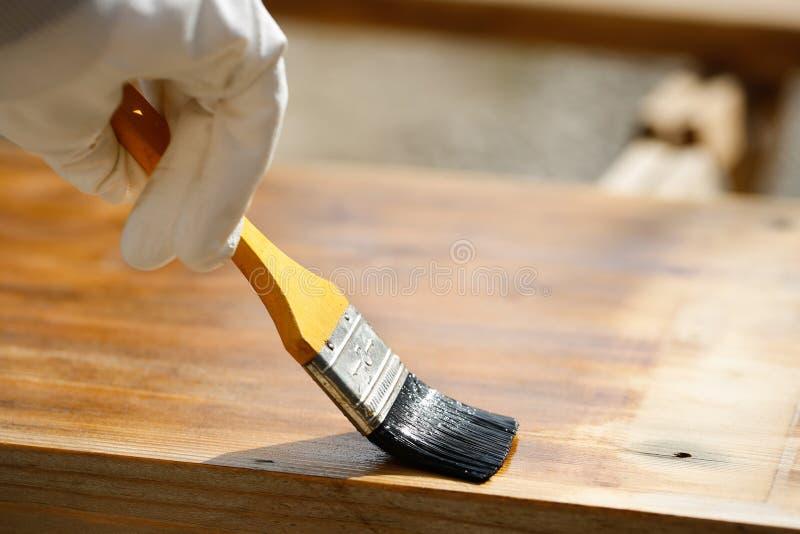 Художник крася деревянную поверхность, защищая древесину стоковые фотографии rf
