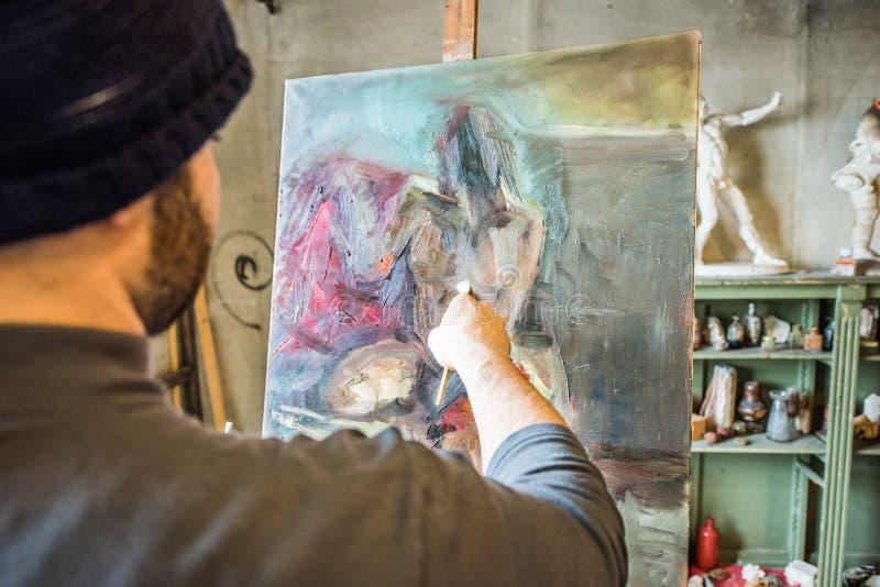 Художник крася шедевр на его студии - близкой поднимающей вверх съемке стоковые изображения rf