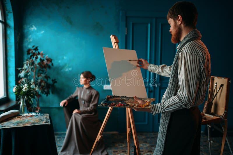 Художник с палитрой и щетка перед мольбертом стоковая фотография rf