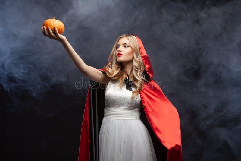 Хэллоуинская ведьма с вырезанной пумкинской и волшебным дымом Красивая молодая удивленная женщина в колдунах шляпа и костюм держа стоковое фото