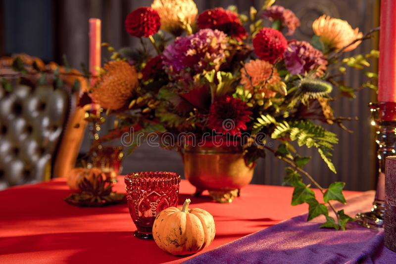 Хэллоуинский стол, празднично украшенный цветами, свечи свечи свечи, тыквочные очки с вином стоковые фотографии rf