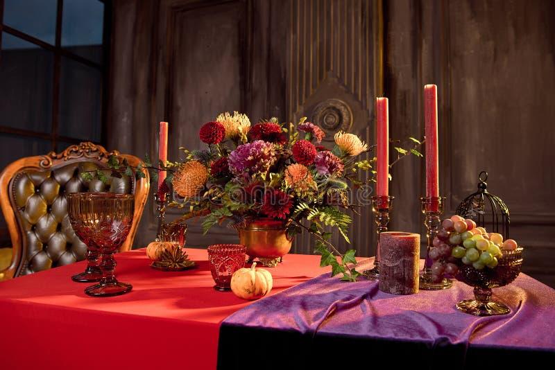 Хэллоуинский стол, празднично украшенный цветами, свечи свечи свечи, тыквочные очки с вином стоковая фотография