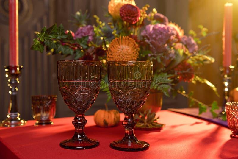 Хэллоуинский стол, празднично украшенный цветами, свечи свечи свечи, тыквочные очки с вином стоковое фото rf