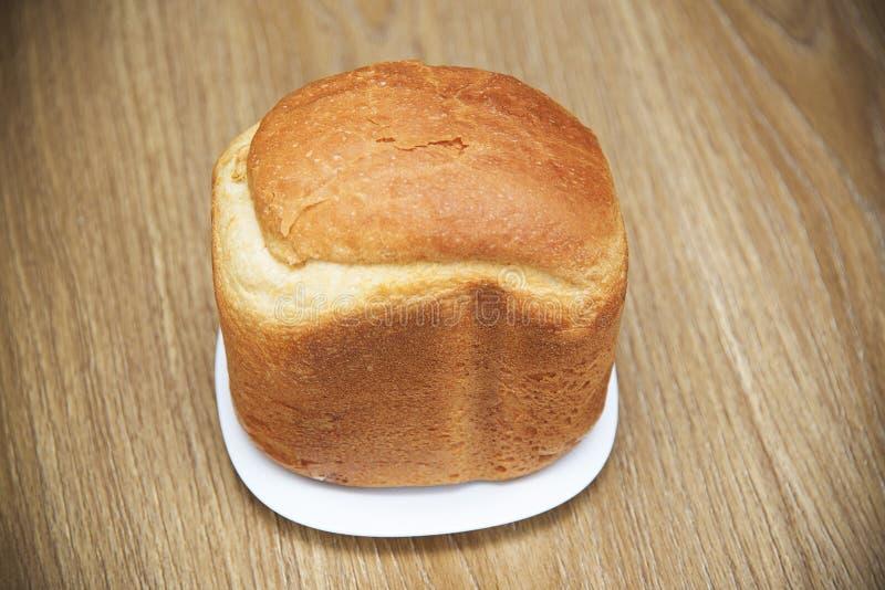 Хлебец белого свежего хлеба на плите на деревянном столе стоковое фото