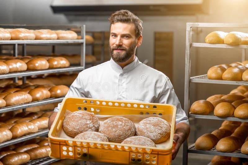 Хлебопек держа хлебы на производстве стоковая фотография rf