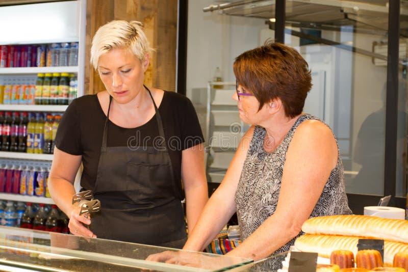 Хлебопек 2 женщин, продавщица в хлебопекарне продавая свежие продукты хлебопекарни стоковое фото