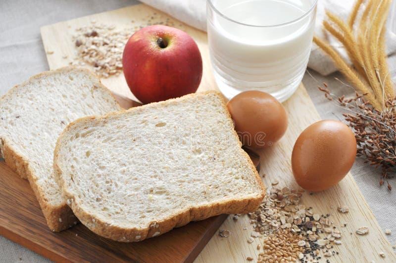 Хлеб всей пшеницы на деревянной доске с молоком на предпосылке стоковые изображения rf