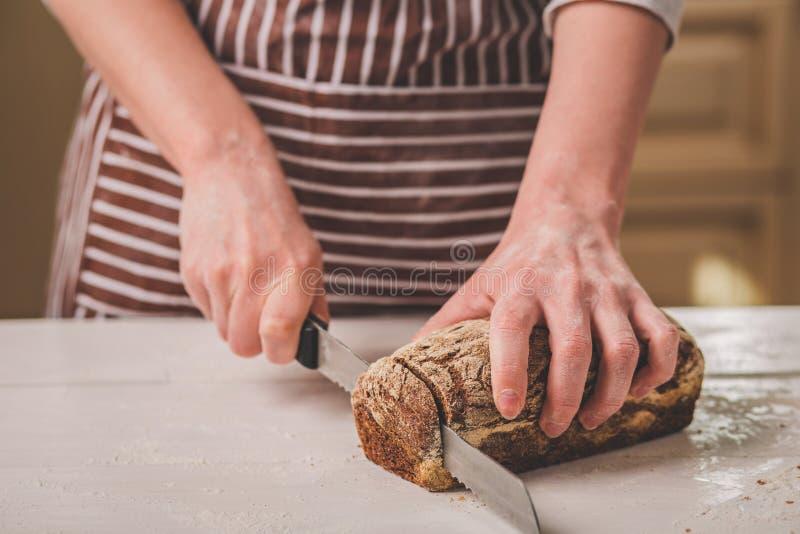 Хлеб вырезывания женщины на деревянной доске хлебопеков Продукция хлеба стоковая фотография