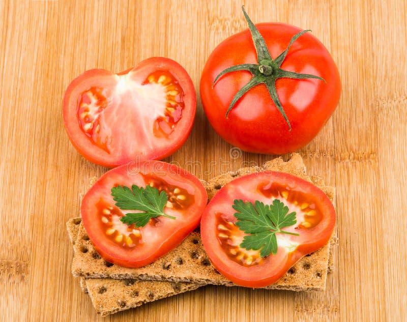Хлеб и томат пшеницы хрустящий на бамбуковой доске стоковая фотография
