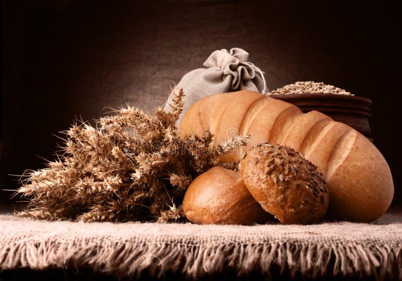 Хлеб, мешок муки и уши образовывают натюрморт стоковое фото