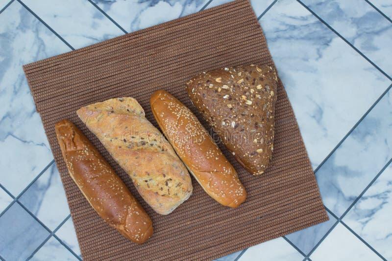 Хлеб с семенами подсолнуха и семенами сезама на плетеной салфетке стоковые фото