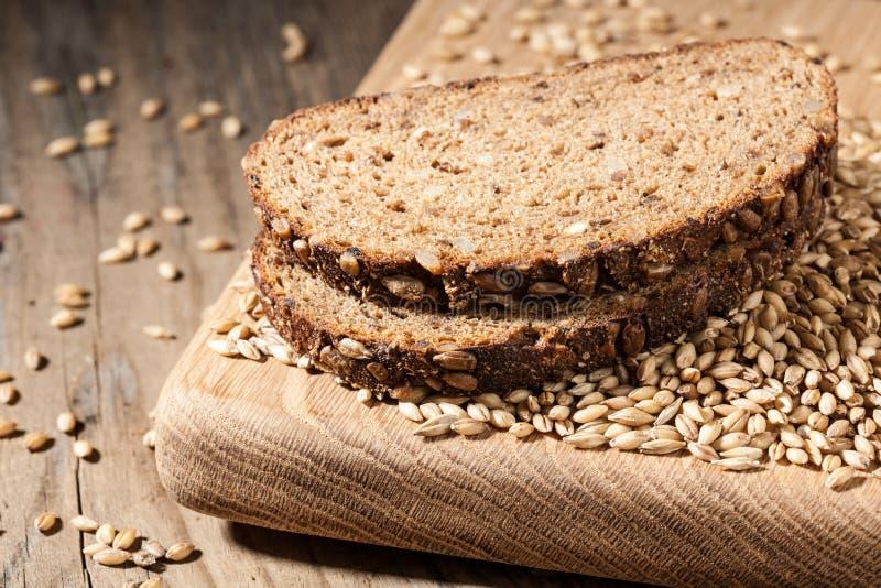 Хлеб Rye с семенами на разделочной доске на деревянном столе стоковая фотография rf