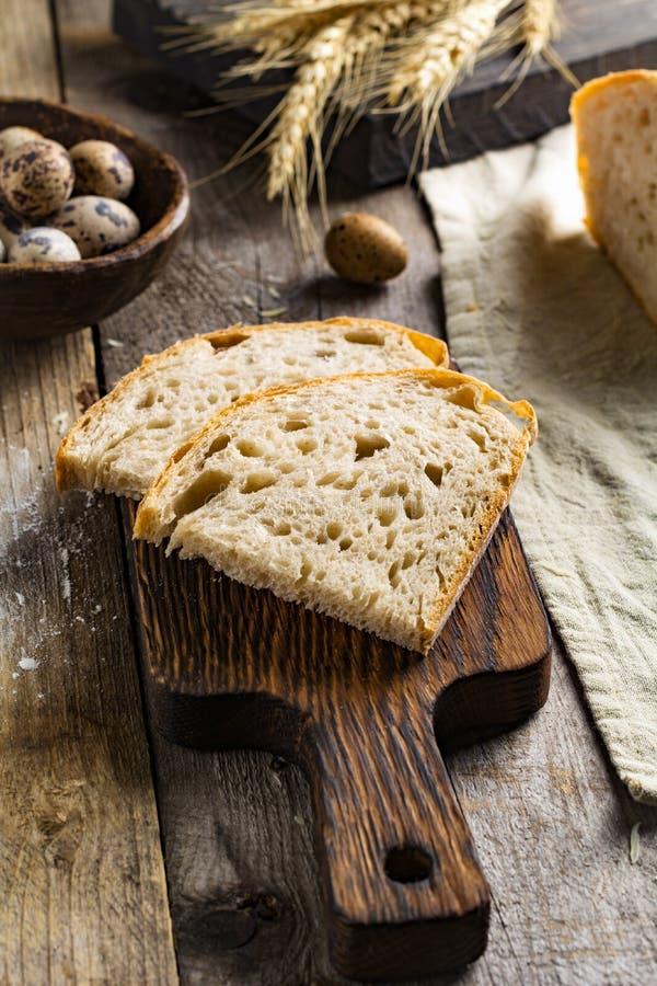 Хлеб Sourdough, яичка триперсток на текстурированном деревянном столе стоковые изображения rf