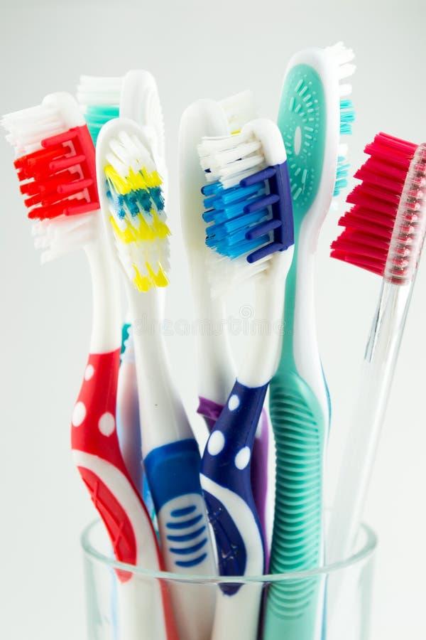 Цветастые зубные щетки в стекле воды стоковые фотографии rf